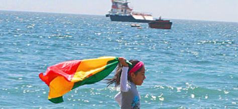 Una niña flamea la tricolor boliviana en la costa del Pacífico.