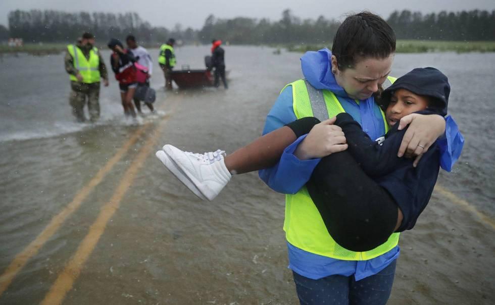 Voluntarios rescatan tres niños de su casa inundada en James City, EE UU.