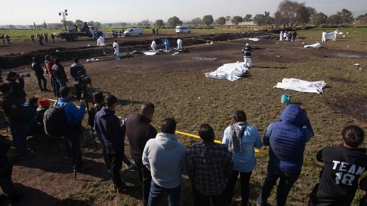 Expertos forenses registran la zona cerca de una toma clandestina de gasolina de Petróleos Mexicanos (Pemex) que explotó este sábado, en Tlahuililpan, Hidalgo (Foto: EFE/ MLA)