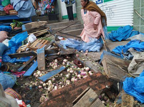 Una comerciante observa las tarimas destrozadas debido al accidente de un bus. Foto: Miguel Alapati