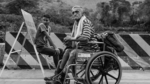 José Agustín López, de 52 años, junto a su hijo Víctor Enrique López, de 18, a lo largo de la carretera que une Cúcuta y Pamplona, en el departamento de Norte de Santander, Colombia, el 11 de febrero de 2019