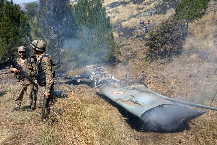 Soldados de Pakistán junto a los restos que, afirman, pertenecen a un avión de la India (AFP)