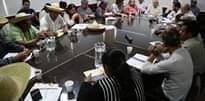 La imagen puede contener: 3 personas, personas sentadas y tabla