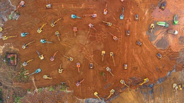 La toma aérea de más de 50 máquinas que trabajan sin descanso para acondicionar el suelo del sitio elegido para construir un hospital en Wuhan, China (Foto de STR/ AFP/ China OUT)