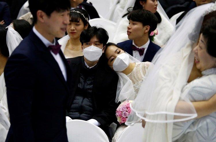 Una pareja usando máscaras para protegerse del coronavirus en una iglesia en Corea del Sur (REUTERS/Heo Ra)