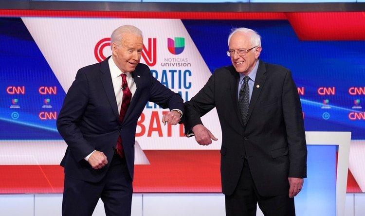 Joe Biden y Bernie Sanders se saludan con el codo en el debate de domingo. REUTERS/Kevin Lamarque