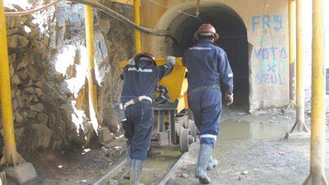 Dos trabajadores mineros se internan a uno de los socavones de la mina estatal Huanuni.