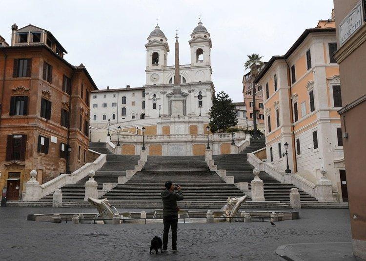 Un hombre toma una fotografía en la turística Via Condotti sin gente alrededor mientras el gobierno italiano continúa con las medidas restrictivas de movimiento para combatir el brote de coronavirus en Roma, Italia, el 14 de marzo de 2020 (REUTERS/Alberto Lingria)