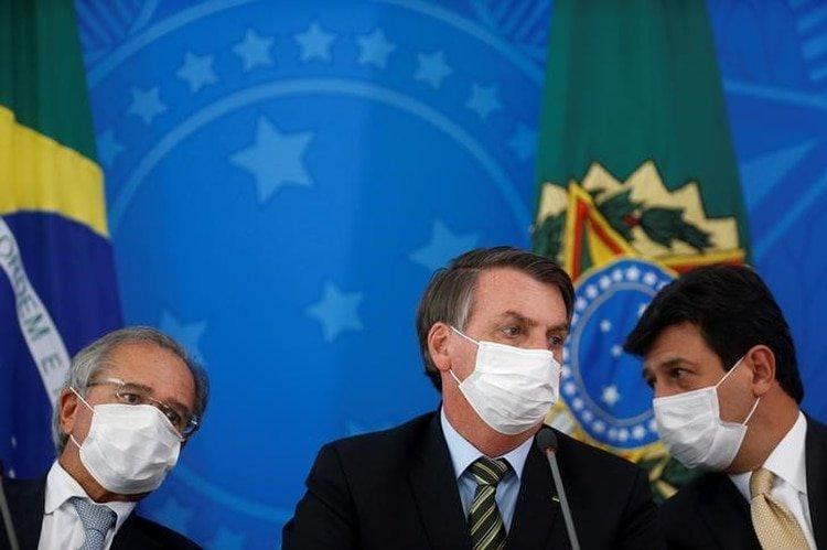 El presidente de Brasil, Jair Bolsonaro, el ministro de Salud, Luiz Henrique Mandetta, y el ministro de Economía, Paulo Guedes, visten mascarillas protectoras mientras asisten a una conferencia de prensa para anunciar medidas para contener el avance del brote de coronavirus. (REUTERS/Adriano Machado)
