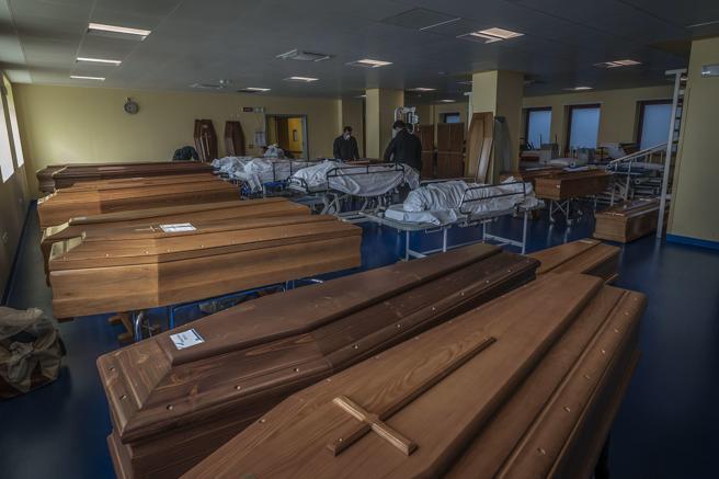 Trabajadores llevan cuerpos de víctimas de coronavirus en Bérgamo