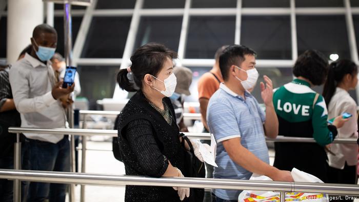 Foto de personas en aeropuerto con mascarilla