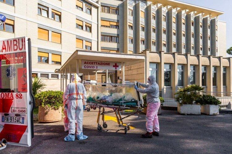 FOTO DE ARCHIVO: Un paciente con coronavirus llega en camilla al Hospital Colombo Covid, que ha sido asignado como uno de los nuevos hospitales de tratamiento de coronavirus en Roma, luego de ser trasladado por trabajadores médicos con trajes blancos protectores del Hospital Gemelli, en Roma, Italia. , 16 de marzo de 2020. (Gemelli a través de REUTERS)