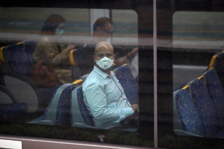 Un viajero que usa una máscara facial se sienta en un tren durante la hora pico de la mañana después de que Nueva Gales del Sur comenzó a cerrar negocios no esenciales y avanzó hacia sanciones severas para forzar el autoaislamiento a medida que la propagación de la enfermedad por coronavirus (Reuters)