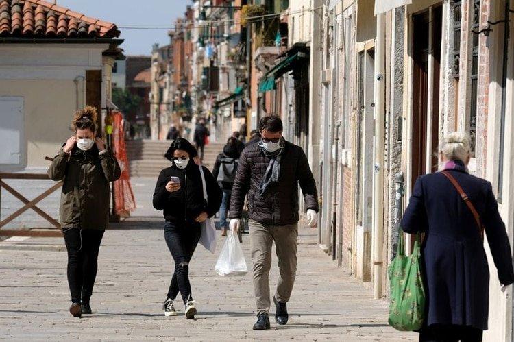 Ciudadanos usan máscaras protectoras en las calles de Venecia durante la actual emergencia por la enfermedad COVID-19, provocada por el coronavirus, en Venecia, Italia. 25 de marzo, 2020. REUTERS/Manuel Silvestri