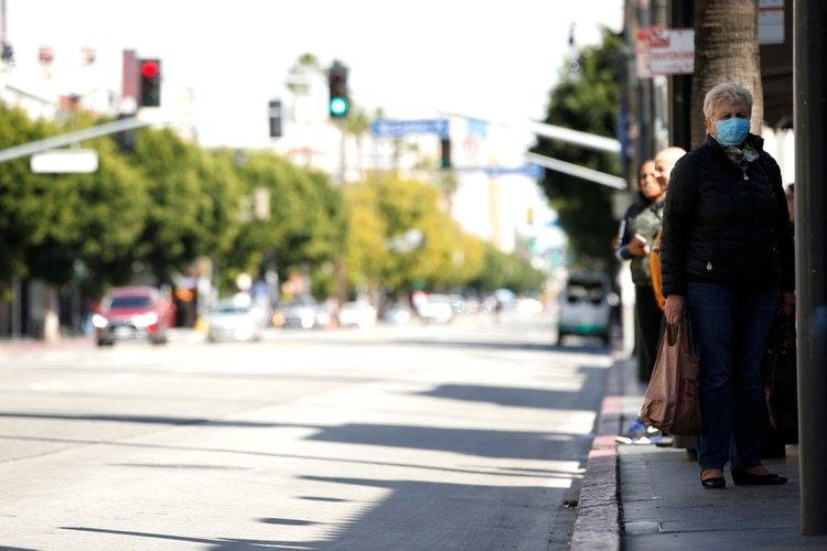 Una persona con una máscara facial espera en la acera durante el brote global de la enfermedad por coronavirus (COVID-19) en Los Ángeles, California, EE. UU., 18 de marzo de 2020. REUTERS / Mario Anzuoni