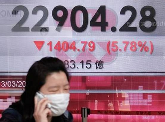 Una mujer con una máscara facial como medida de precaución contra el coronavirus pasa por delante de un tablero de exhibición del mercado de valores de Hong Kong (Foto de Anthony WALLACE / AFP)