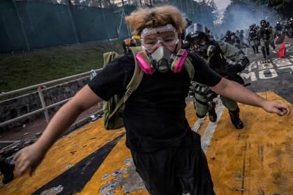 Un manifestante antigubernamental es perseguido por policías antidisturbios después de escaramuzas en la Universidad China de Hong Kong, el 12 de noviembre de 2019 (REUTERS/Tyrone Siu)