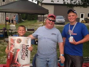Team owner Jim Howe (center) celebrates twin podiums and some really nifty prizes with drivers Eli Fox (left) and Bransten Peavler at the 12th annual Goodland Grand Prix