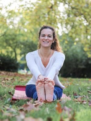 Medha professeure de yoga assise sur tapis de yoga en extérieur