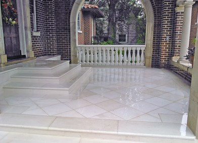 Masonry cast stone pavers and steps with a cast stone balustrade rail.