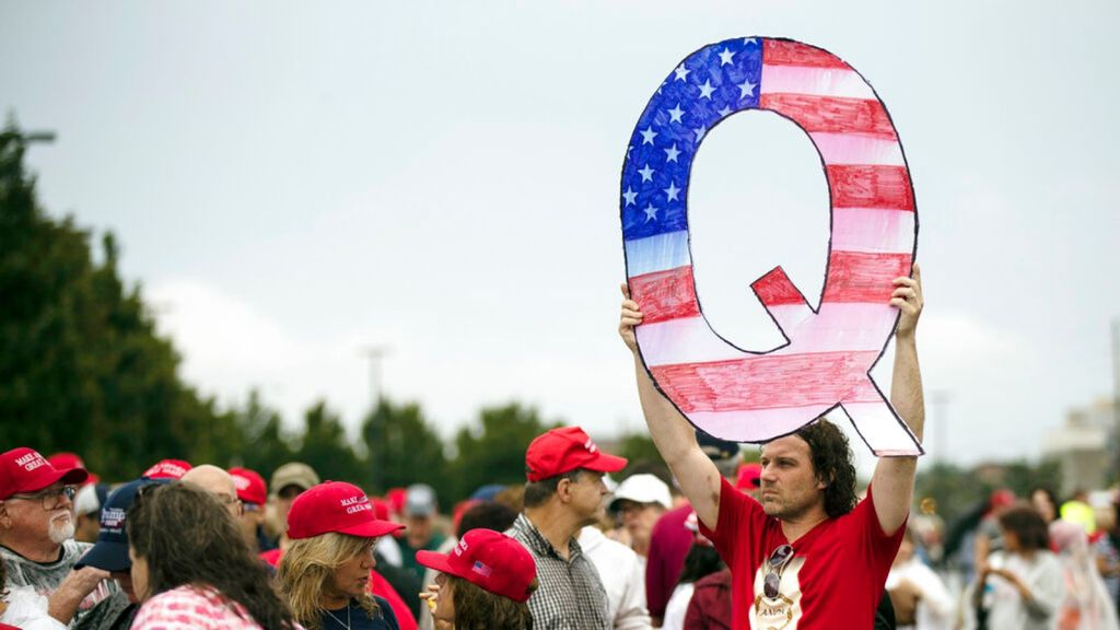 FILE - In this Aug. 2, 2018, file photo, a protesters holds a Q sign waits in line with others to enter a campaign rally with President Donald Trump in Wilkes-Barre, Pa. Facebook and Twitter promised to stop encouraging the growth of the baseless conspiracy theory QAnon, which fashions President Donald Trump as a secret warrior against a supposed child-trafficking ring run by celebrities and government officials. But the social media companies haven't succeeded at even that limited goal, a revie