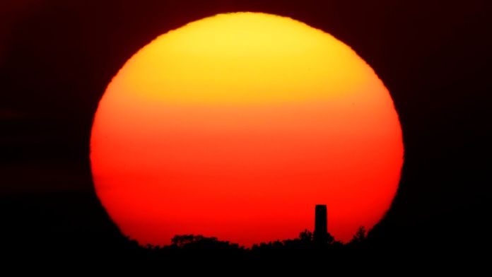 A distant smokestack stands against the setting sun in Kansas City, Mo., Friday, June 26, 2020. Pic: AP