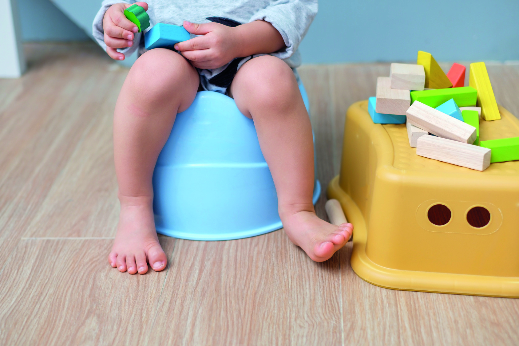 Closeup of legs of cute little Asian 18 months old toddler baby boy child sitting on potty playing with wooden blocks toy. Kid playing with educational toy & Toilet training concept. - Selective focus