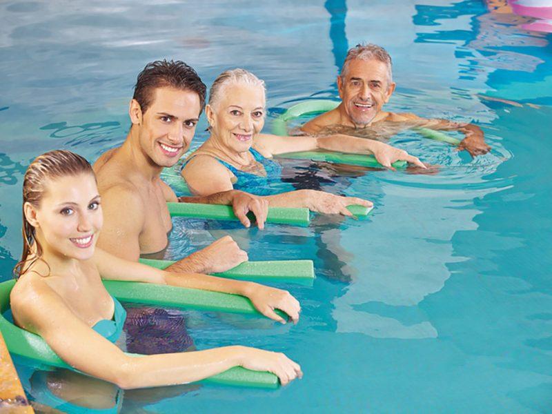 Glückliche Gruppe mit Schwimmnudeln beim Aquafitness im Schwimmbad