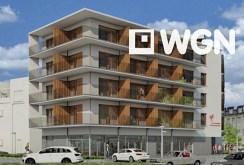 widok z boku na apartamentowiec nad morzem, w którym mieści się oferowany apartament do sprzedaży