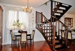 zdjęcie prezentuje schody na górny poziom oraz jadalnię na drugim planie w willi do sprzedaży w okolicy Warszawy