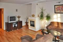 zdjęcie prezentuje fragment salonu z kominkiem w ekskluzywnym apartamencie do wynajęcia w okolicy Szczecina