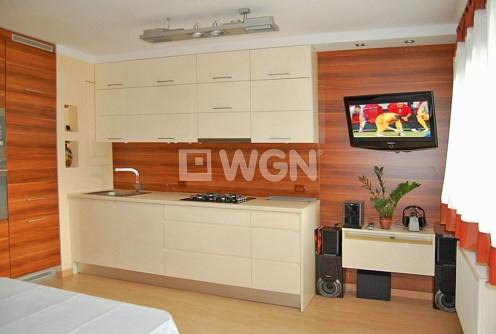 na zdjęciu aneks kuchenny oraz fragment salonu w luksusowym apartamencie na sprzedaż w Szczecinie