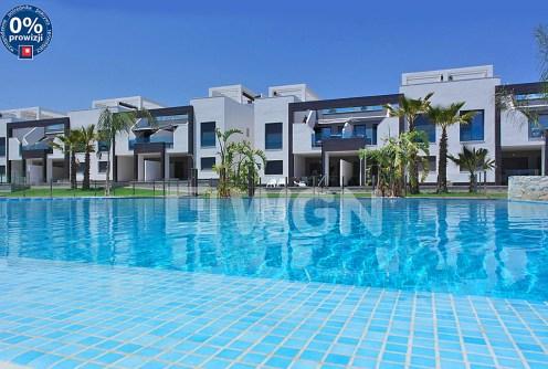 widok od strony basenu na luksusowy apartamentowiec w Hiszpanii, w którym znajduje się ekskluzywny apartament na sprzedaż