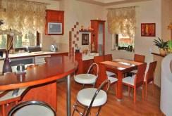 widok na jadalnię oraz fragment kuchni w luksusowej willi na sprzedaż w okolicy Częstochowy