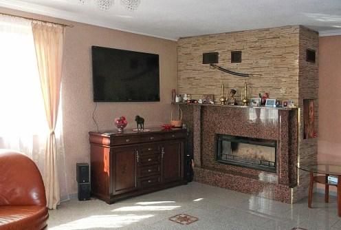 zdjęcie prezentuje salon z kominkiem i sprzętem rtv w luksusowej willi do sprzedaży w okolicy Wałbrzycha