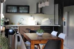 na pierwszym planie jadalnia, w oddali kuchnia w luksusowym apartamencie w Tczewie na sprzedaż