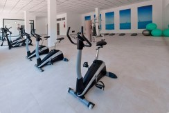wyposażona siłownia w częściach wspólnych apartamentowca, w którym znajduje się oferowany na sprzedaż ekskluzywny apartament Hiszpania (La Zeni)
