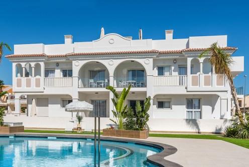 widok od strony basenu na ekskluzywny apartamentowiec, w którym znajduje się oferowany na sprzedaż luksusowy apartament Hiszpania (Ciudad Quesad)