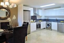 na pierwszym planie jadalnia oraz aneks kuchenny w ekskluzywnym apartamencie na sprzedaż Hiszpania (Costa Blanca Torrevieja, Punta Prima)