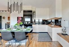 na pierwszym planie kuchnia i jadalnia w luksusowym apartamencie na sprzedaż Gdańsk