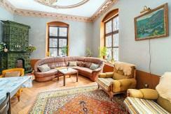 przeciwległa strona salonu z kominkiem w luksusowym pałacu do sprzedaży dolnośląskie