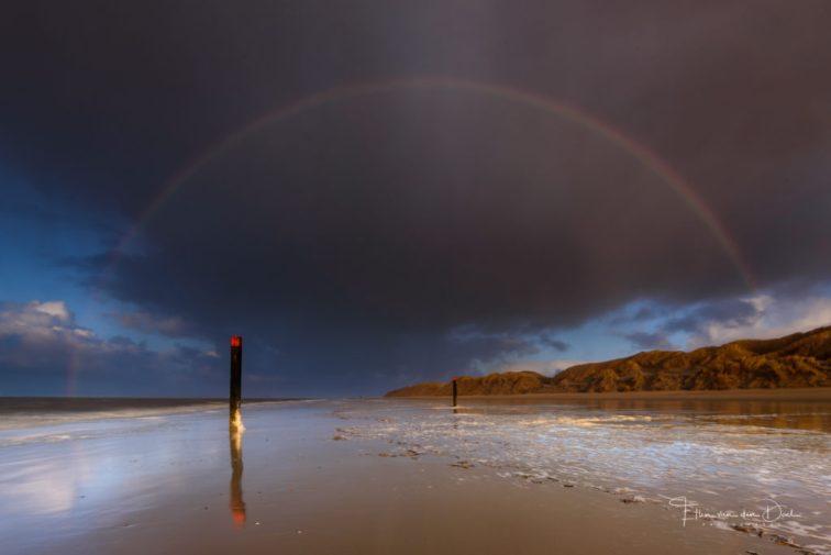 Een regenboog boven het strand