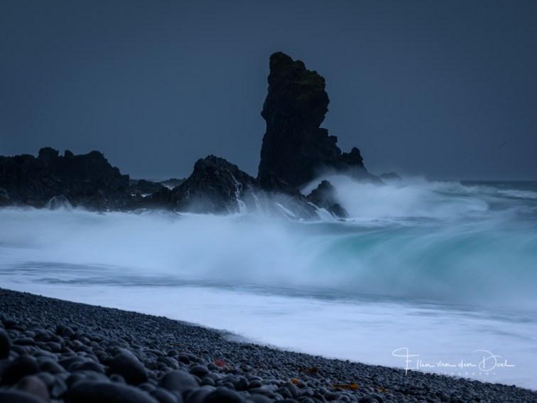 Golven slaan op de zwarte kust