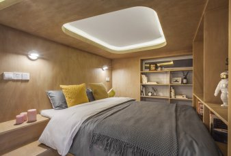 a-look-inside-the-cozy-bedroom-lined-in-wood-veneer-a-recessed-skylight-inspired-lighting-feature-helps-keep-the-space-from-feeling-too-snug
