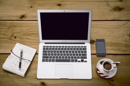 Estudar Programação: Uma mesa com um notebook, um caderno de anotações, um celular e uma xícara de café.
