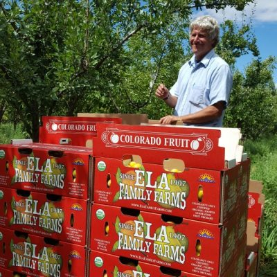 Ela Family Farms Steve Ela with Red fruit boxes in orchard