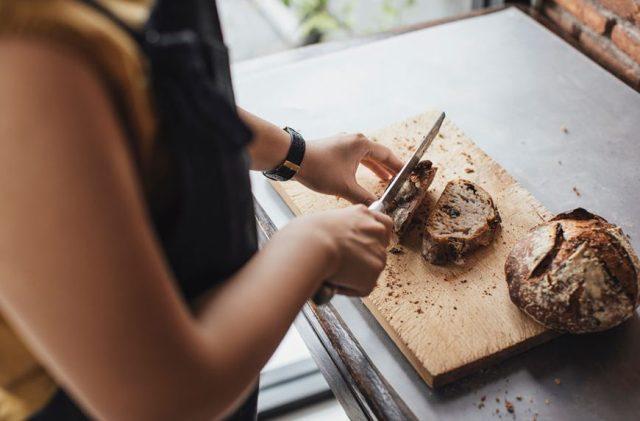 Stocksy-woman-cutting-bread-Lumina