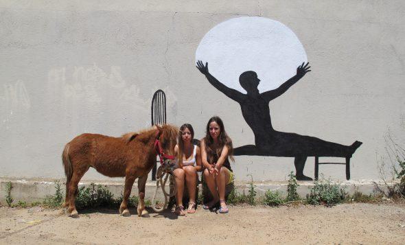 Alejandra y Judit con su pony Pitufa junto a uno de sus grafitis favoritos -obra de Cyop & Kaf- en el polígono de Vilaroja junto a la Font de la Pólvora en Girona. Foto: Manuel Cuéllar.