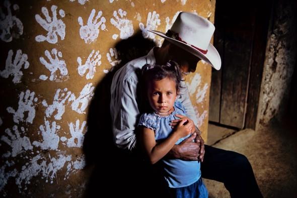 Un hombre y su nieta frente a una pared decorada con huellas de manos. La Fortuna. Honduras, 2004. Foto: Steve McCurry.