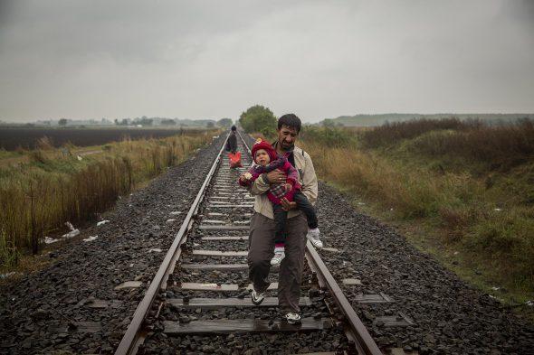 Un padre y su hijo caminan por las vías del tren en Hungría, a pocos metros de la frontera con Serbia.